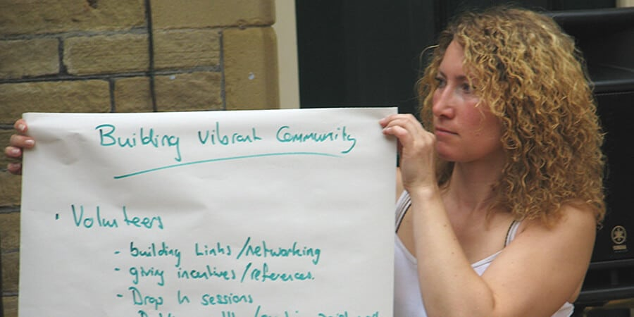 Woman at a community meeting, holding up a 'Building Vibrant Community' ideas sheet